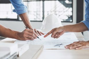 Hands of architect or engineer working on blueprint meeting for